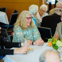 Guests sitting around a table at the Retiree Reception.